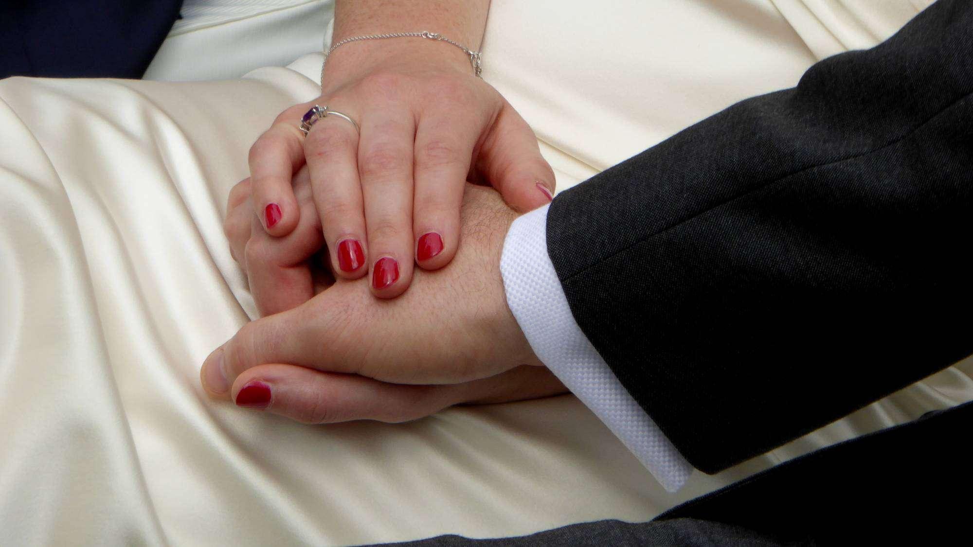 Eheleute zeigen mit ihren Haenden ihre Liebe