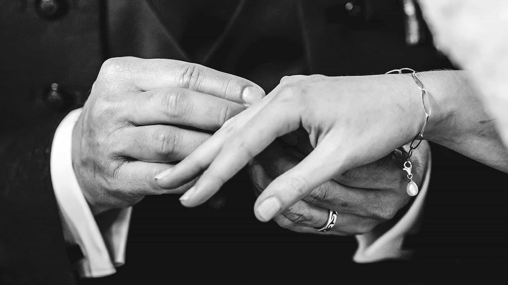 Der Bräutigam steckt der Braut den Ring an den Finger