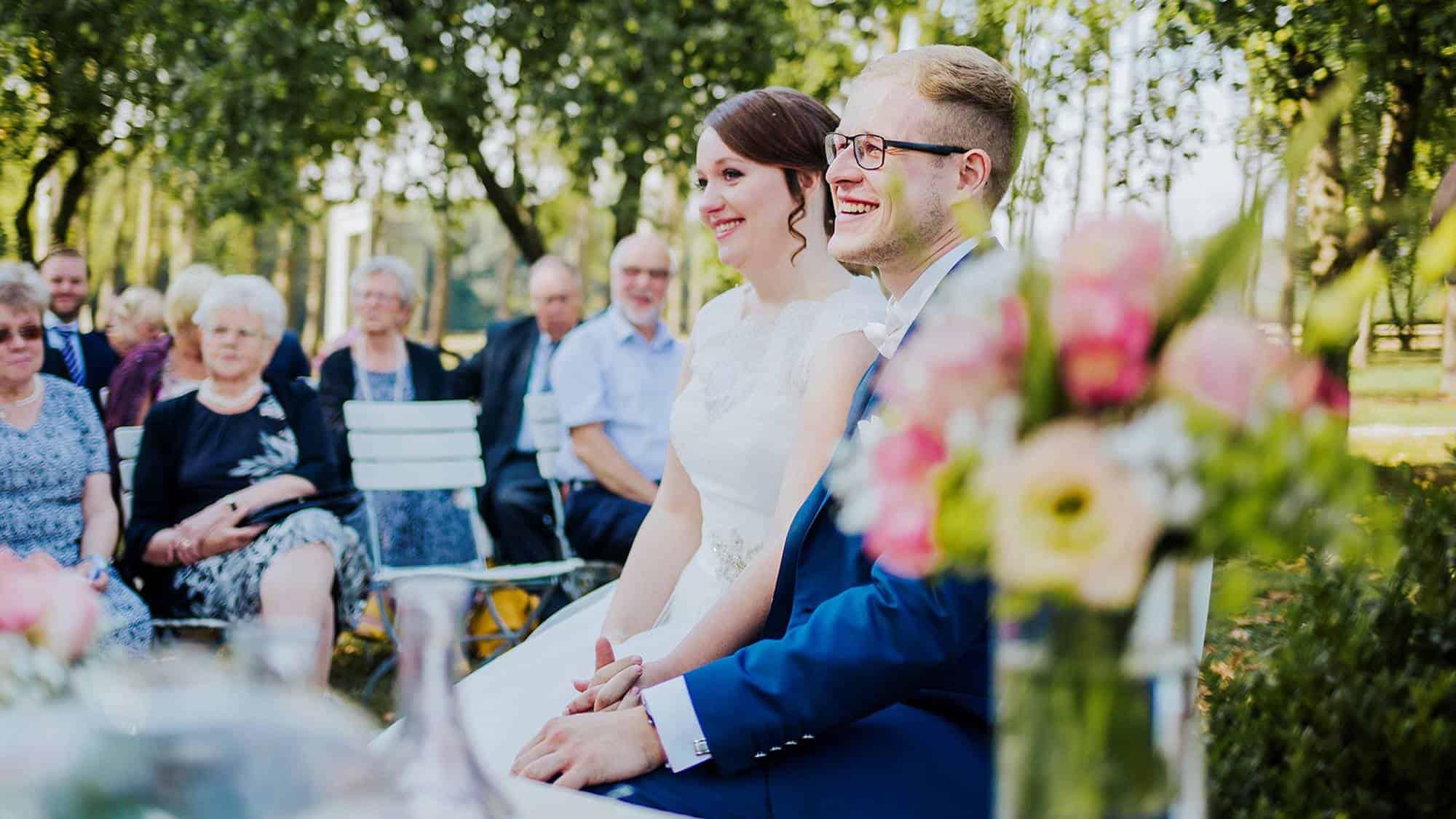 Das Brautpaar sitzt den Gästen zugewandt