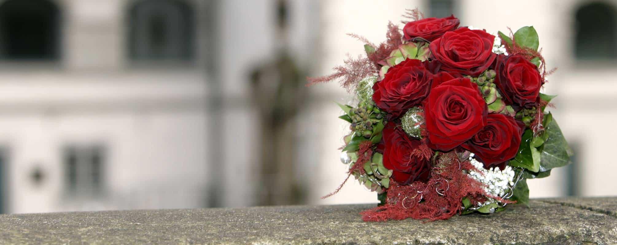 Brautstrauß roten Rosen liegt auf einer Mauer