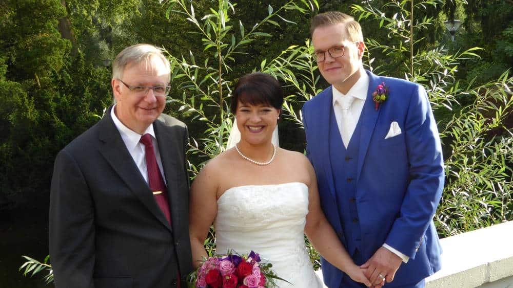 Ein glückliches Paar mit ihrem freien Redner Reginald Müller, der die freie Trauung geleitet hat