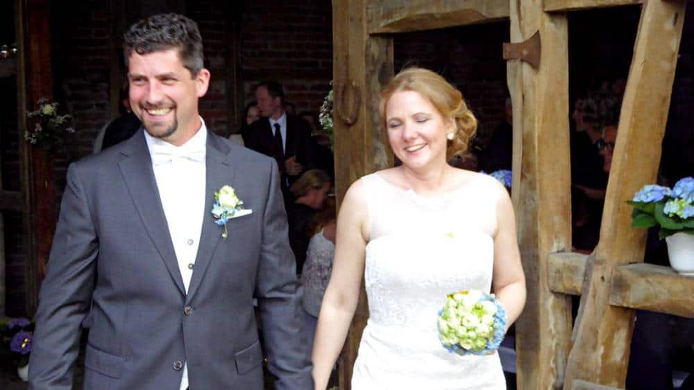 Brautpaar kommt nach der Hochzeitszeremonie aus der Scheune