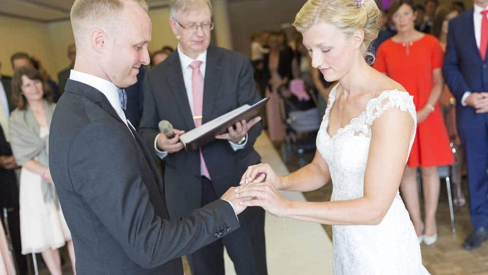 Die Eheleute stecken den Ring an den Finger des Partners