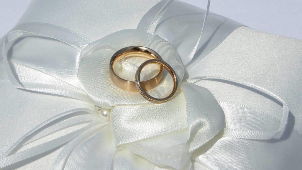 Goldene Eheringe liegen auf einem Ringkissen